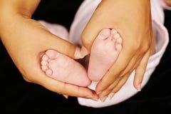 Dedos do pé do bebê realizados em um coração Imagens de Stock