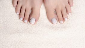 Dedos do pé fêmeas com o pedicure branco na toalha de terry do marfim, fim acima P?s desencapados da mulher imagem de stock