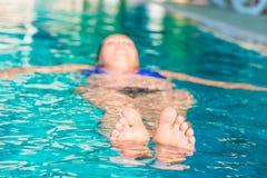 Dedos do pé que espreitam fora da água Imagens de Stock