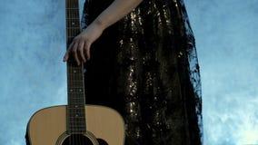 Dedos do ` s da menina no close-up das cordas A mão fêmea corre a partir de baixo o fretboard da guitarra acústica Dia da música filme
