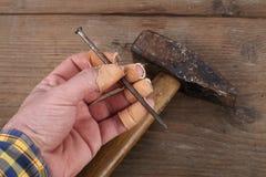 Dedos e martelo da mão do carpinteiro Imagens de Stock Royalty Free