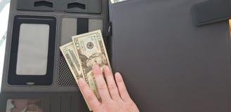 dedos em 20 dólares de contas sobre o dobrador preto do bolso imagem de stock