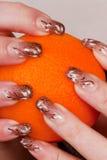 Dedos en una naranja Imágenes de archivo libres de regalías