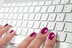 Dedos fêmeas que tocam em um teclado do metal branco. Fotografia de Stock Royalty Free
