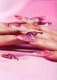 Dedos humanos con la uña larga sobre color de rosa Imagen de archivo
