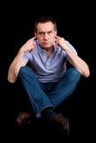 Dedos irritados do homem em equipado com pernas transversal de escuta das orelhas Imagens de Stock Royalty Free