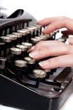 Dedos na máquina de dactilografia do vintage no branco Foto de Stock Royalty Free