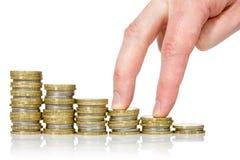 Dedos que andam acima em pilhas de moedas Foto de Stock