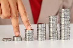 Dedos que andam acima em pilhas de moedas Imagem de Stock