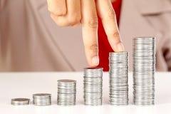 Dedos que andam acima em pilhas de moedas Imagem de Stock Royalty Free