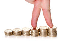Dedos que andam acima em pilhas de moedas de uma libra Fotos de Stock Royalty Free