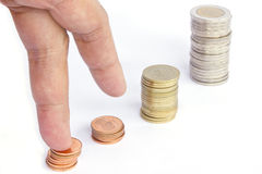 Dedos que andam acima em pilhas de moedas no fundo branco Growt Foto de Stock Royalty Free