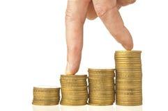 Dedos que andam para baixo em pilhas de moedas Fotografia de Stock