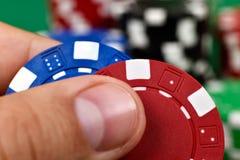 Dedos que guardam duas microplaquetas de pôquer Fotografia de Stock