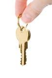 Dedos que mantêm chaves douradas isoladas Fotografia de Stock