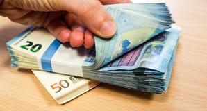 Dedos que passam rapidamente através de uma pilha de dez contas do Euro, com uma outra pilha dos anos 50 Fotografia de Stock