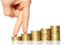 Dedos que recorren para arriba en pilas de monedas Foto de archivo libre de regalías