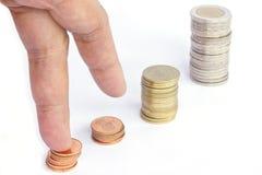 Dedos que recorren para arriba en pilas de monedas en el fondo blanco Growt Foto de archivo libre de regalías