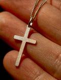 Dedos que sostienen el collar cruzado de plata Fotos de archivo libres de regalías