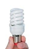 Dedos que sostienen la bombilla ahorro de energía. Fotografía de archivo libre de regalías