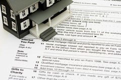 Deduct mortgage interest on taxes. A model house sitting on tax papers, Deduct mortgage interest on taxes stock photo
