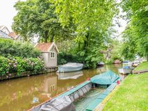 Canal with boats in old town of Broek in Waterland, Netherlands. Dee canal with boats in old village of Broek in Waterland north of Amsterdam, Noord-Holland Royalty Free Stock Images