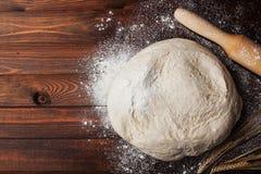 Deeg met hierboven bloem, deegrol, tarweoren op rustieke houten lijst van Eigengemaakt gebakje voor brood of pizza De achtergrond