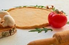 Deeg voor pizzabasis klaar voor het koken en natuurlijke ingrediënten voor vegetarische pizza op de witte achtergrond met een dee Royalty-vrije Stock Foto's