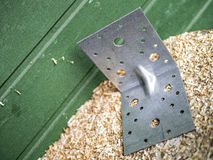 90 deegrees steel perforated angle fastener with shavings. 90 deegrees steel perforated angle fastener near wood wall standing on a shavings stock photo