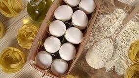 Deegwaren, eieren, olie en bloem op houten achtergrond stock videobeelden