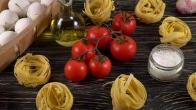 Deegwaren, eieren, olie, tomaten en knoflook op houten achtergrond stock videobeelden