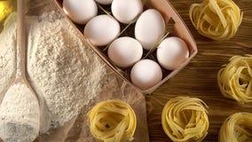 Deegwaren, eieren, olie, tomaten, knoflook en bloem op houten achtergrond stock videobeelden