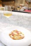 Deegwaren met bacon in roomsaus het dienen met witte wijn Royalty-vrije Stock Foto