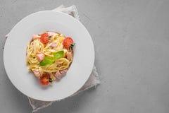Deegwaren met forel en tomaat in witte plaat op lichte achtergrond Heerlijke mediterrane lunch stock afbeeldingen