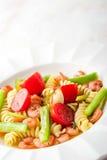 Deegwaren met groenten en garnalen op de witte verticaal als achtergrond Royalty-vrije Stock Fotografie