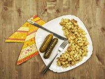 Deegwaren met vlees en gebraden uien en groenten in het zuur op een witte plaat Royalty-vrije Stock Foto's