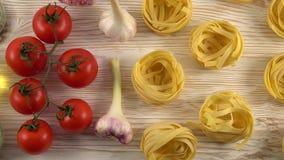 Deegwaren, olie, tomaten en knoflook op houten achtergrond stock footage