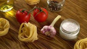 Deegwaren, olie, tomaten en knoflook op houten achtergrond stock videobeelden