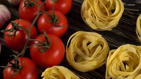 Deegwaren, olie, tomaten en knoflook op houten achtergrond stock video
