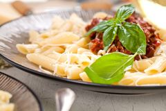 Deegwaren Penne met Tomaten Bolognese Saus, Parmezaanse kaaskaas en Basilicum stock afbeelding