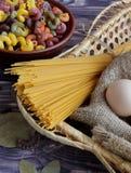 Deegwaren, spaghetti en eieren op een donkere achtergrond en een bamboemand royalty-vrije stock afbeelding