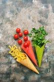 Deegwaren, tomaten en peterselie in een wafelkegel van het roomijs r De hoogste vlakke mening, legt stock foto's