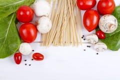 Deegwaren, tomaten, paddestoelen en peper op een witte houten achtergrond Stock Afbeelding