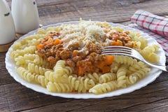 Deegwarenfusilli met bolognese saus van het tomatenrundvlees op houten lijst Stock Fotografie