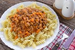 Deegwarenfusilli met bolognese saus van het tomatenrundvlees op houten lijst Royalty-vrije Stock Foto's