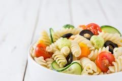 Deegwarensalade met groenten in kom op wit hout Royalty-vrije Stock Foto