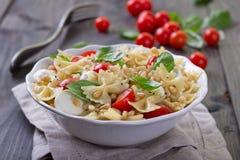 Deegwarensalade met tomaat, mozarella, pijnboomnoten en basilicum Stock Foto's