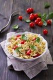Deegwarensalade met tomaat, mozarella, pijnboomnoten en basilicum Stock Afbeeldingen