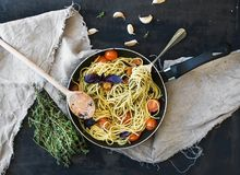 Deegwarenspaghetti met pestosaus, basilicum, kers-tomaten, knoflook en thyme in een kokende pan stock foto's
