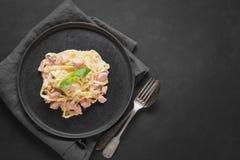 Deegwarentagliatelle met forel en room op zwarte achtergrond Heerlijke mediterrane lunch stock foto